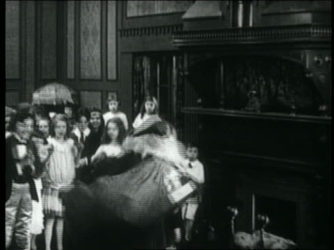 B/W 1918 crowd of children cheering for Santa Claus by fireplace