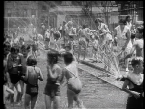 vidéos et rushes de b/w 1939 crowd of children playing in fountain in park / nyc / travelogue - maillot une pièce