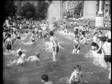 b/w 1939 crowd of children playing in fountain in washington square park / nyc / travelogue - greenwich village stock videos & royalty-free footage