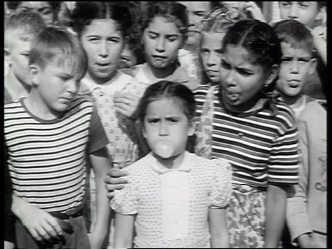 b/w 1947 crowd of children watch as girl blows bubble with gum / newsreel - bubble gum stock videos & royalty-free footage
