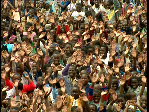 Crowd of children waving in refugee camp set up during Rwandan civil war Democratic Republic of Congo 1994