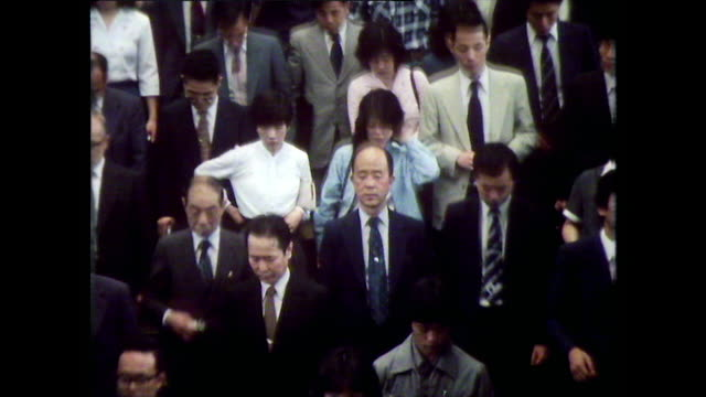 crowd of city workers walking down steps in tokyo; 1981 - bbc archive stock-videos und b-roll-filmmaterial
