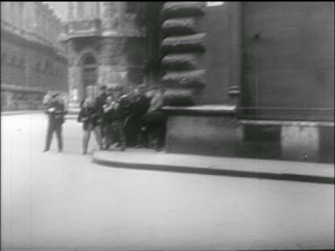crowd of civilians huddled against building firing guns / hungarian uprising - 1956 stock-videos und b-roll-filmmaterial