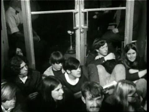 vídeos y material grabado en eventos de stock de crowd of civilians sits in front of the military induction center; police officers arrest protesters. - 1960