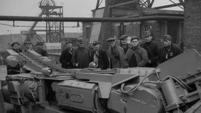 1978 montage crowd of coal miners and coal operators observing the workings of a new joy continuous mining machine on display aboveground / united kingdom - miner stock videos & royalty-free footage