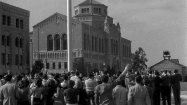 a crowd of college students cheer as they raise a flag on the college campus. - 1938 stock videos & royalty-free footage
