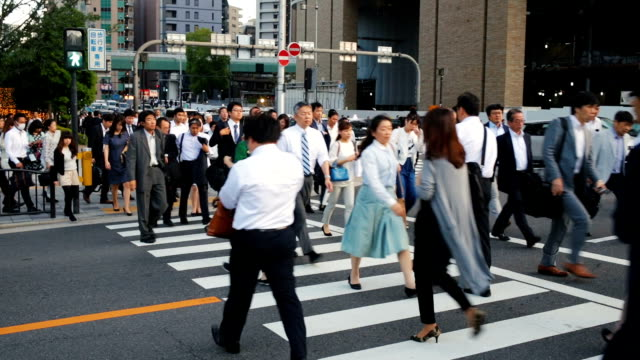 crowd of commuters crossing a busy road in osaka japan - road junction stock videos & royalty-free footage