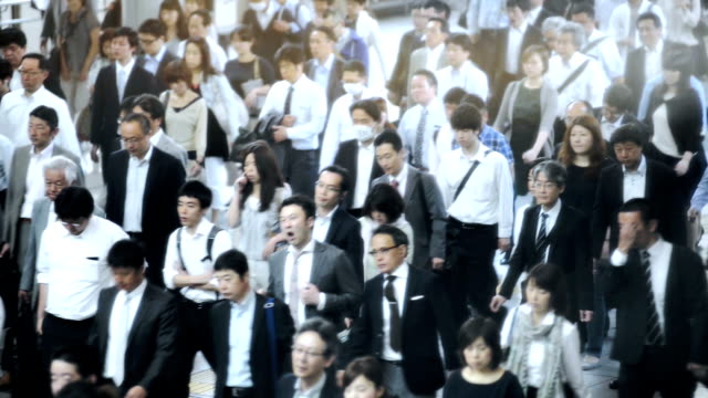 crowd of commuters on their way to work in tokyo - commuter stock videos & royalty-free footage
