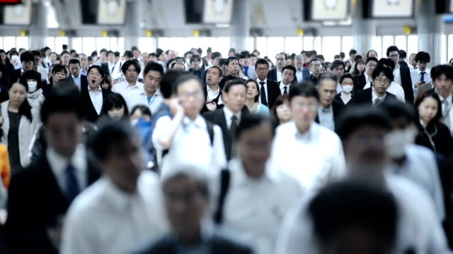 crowd of commuters on their way to work in tokyo - station stock videos & royalty-free footage