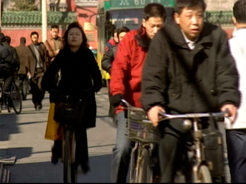 crowd of cyclists and pedestrians heading toward camera on side of street as traffic passes by / pan across street and back / beijing, china - panoramica a schiaffo video stock e b–roll