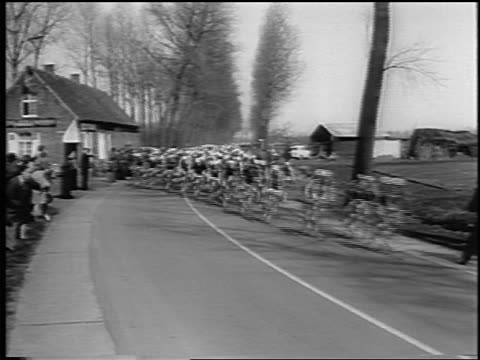 crowd of cyclists coming around curve in tour de france / newsreel - curve stock videos & royalty-free footage