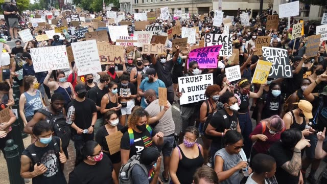 "stockvideo's en b-roll-footage met a crowd of demonstrators standing holding signs wearing face masks chant ""black lives matter"" and march as demonstrators march on constitution avenue... - chanten"