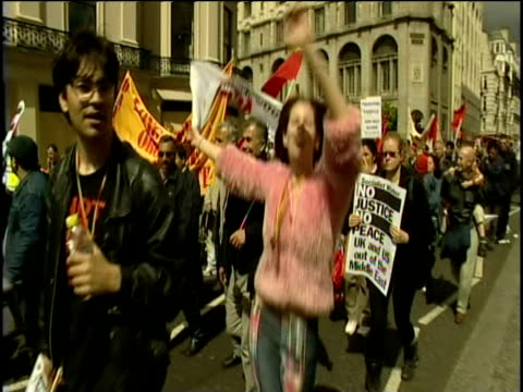 crowd of demonstrators walk through city streets on may day - marciare video stock e b–roll