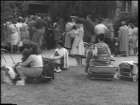 b/w 1961 crowd of east german refugees standing sitting on ground / beginning of berlin wall - 1961 stock-videos und b-roll-filmmaterial