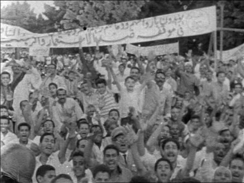 pan crowd of egyptians holding signs raising arms at demonstration / newsreel - non western script stock videos & royalty-free footage