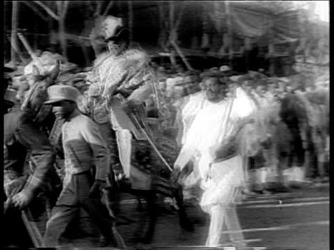 stockvideo's en b-roll-footage met crowd of ethiopians in robes and men on horses running past camera / ethiopian emperor haile selassie on throne wtih two attendants / ethiopian... - 1935