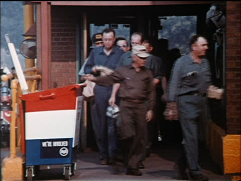 1972 crowd of factory workers exiting building + throwing trash in recycle bin outdoors / industrial - 1972 stock videos and b-roll footage
