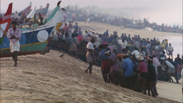 vidéos et rushes de a crowd of fishermen drag fishing boats and nets full of fish on a beach. - pêcheur