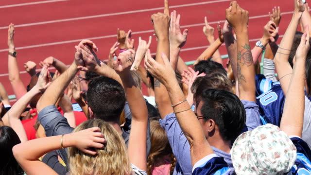 vídeos y material grabado en eventos de stock de ms crowd of football fans cheering with arms raised in stadium rear view - puño
