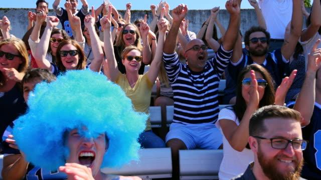 stockvideo's en b-roll-footage met ms ts crowd of football fans sitting in stadium cheering during game - pruik
