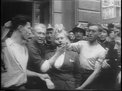 Crowd of French men around French woman woman is held by her hair and neck / closeup on French woman bloody nose being accosted by French men / truck...