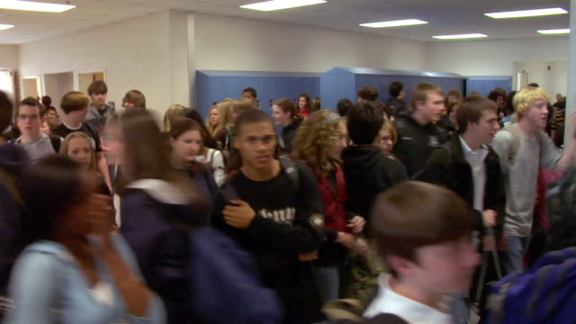 A crowd of high school students fill the hallways between classes.
