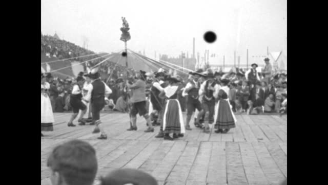 Crowd of hundreds / dancers on stage with people watching / men and women dance around maypole and the women twirl and men drop to one knee /...