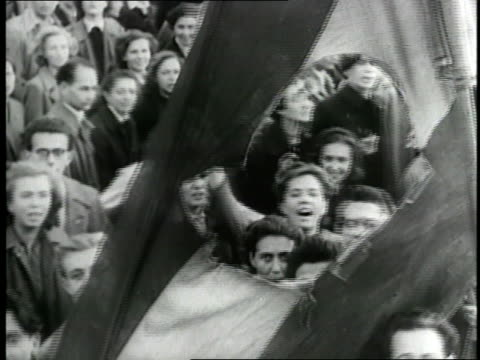 A crowd of Hungarian civilians tears down A Soviet flag and topple a Soviet star during the Hungarian Revolution