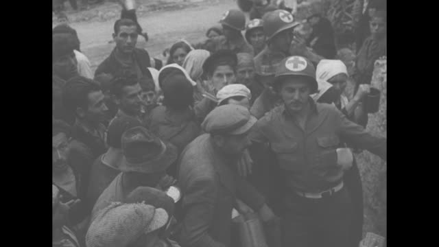 crowd of italian refugees waiting amongst dilapidated buildings for food aid / red cross workers in helmets, holding back refugees / refugees in open... - italian culture stock-videos und b-roll-filmmaterial