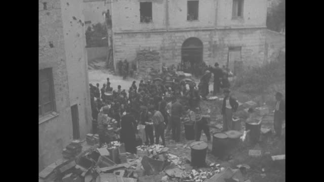crowd of italian refugees waiting amongst dilapidated buildings for food aid / refugees in open area in between buildings, including fires and... - italian culture stock videos & royalty-free footage