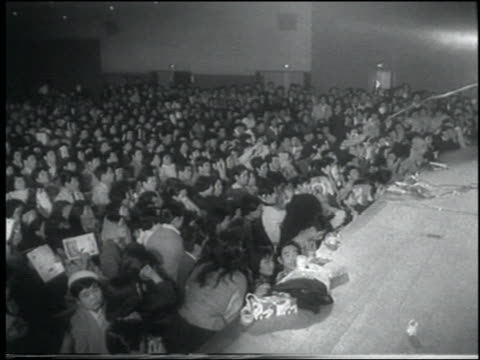 b/w 1958 newsreel crowd of japanese teens in audience at rockabilly concert / tokyo - klassischer rock and roll stock-videos und b-roll-filmmaterial