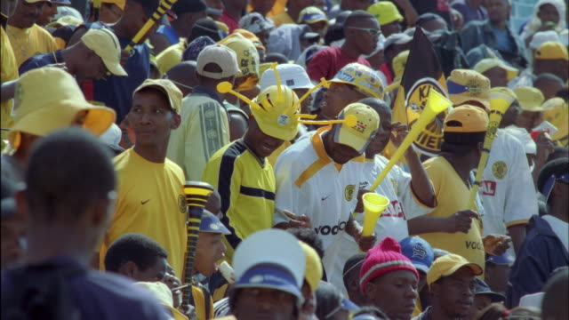 Crowd of Kaizer Chiefs fans dancing and holding vuvuzelas. Available in HD.