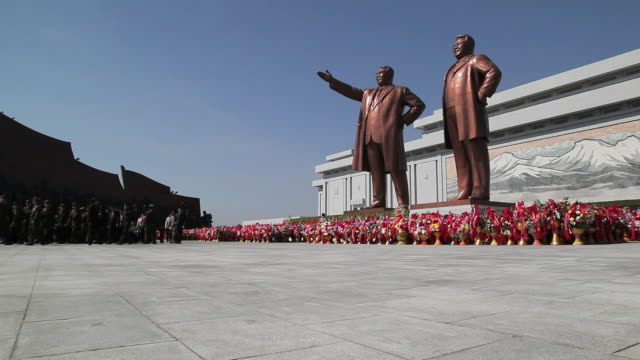 A crowd of Koreans pays respect to the statues of former Presidents Kim Il-Sung and Kim Jong Il at the Mansudae Grand Monument near the Mansudae Assembly Hall on Mansu Hill in Pyongyang, North Korea.