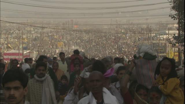 Crowd of Kumbh Mela pilgrims carrying belongings walk through Allahabad, Uttar Pradesh, India