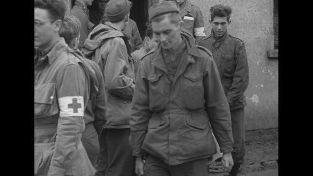 crowd of liberated soldiers runs to a red cross truck after their liberation from pow camp by us troops / medics carry an injured man to ambulance /... - germany stock videos & royalty-free footage