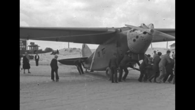 stockvideo's en b-roll-footage met ms crowd of men and women around monoplane a bernardhubert 191 gr called yellow bird on the beach / cu man works on plane engine while smoking a... - 1920 1929