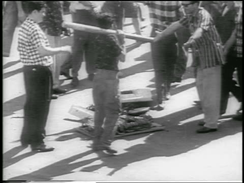 b/w 1959 crowd of men around destroyed machine after revolution / havana / newsreel - 1959 stock-videos und b-roll-filmmaterial