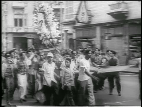 B/W 1959 crowd of men carrying banner float in celebration of revolution / Havana / news