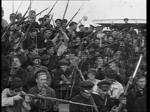 Crowd of men holding rifles sitting together new Bolshevik recruits boarding ship / Russia