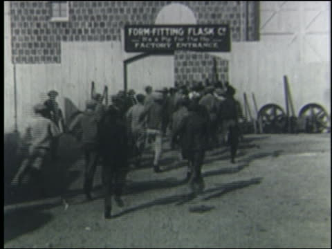 b/w 1923 rear view crowd of men run thru factory gate, turn around + chase man out gate - 1923 stock-videos und b-roll-filmmaterial