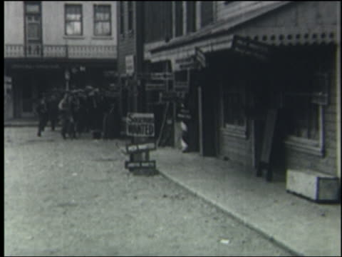 b/w 1923 crowd of men runs around corner + into building on city street - 1923年点の映像素材/bロール