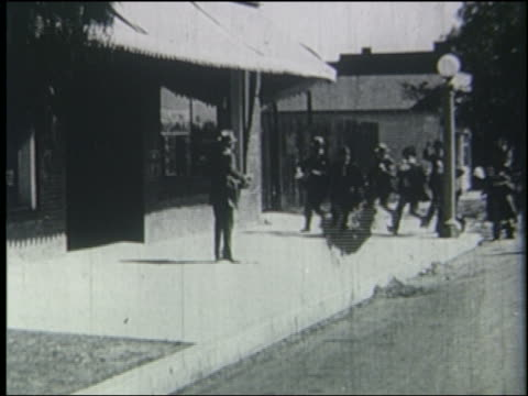 b/w 1923 crowd of men surround man on town sidewalk - 1923 stock videos & royalty-free footage