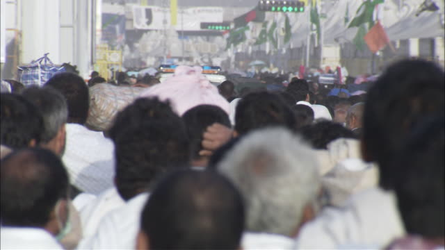 A crowd of Muslim men walks on a street.