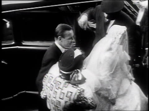 crowd of neighbors gathering to see martha firestone in wedding dress / martha getting out of car in dress and ascending stairs / bridesmaids with... - anno 1947 video stock e b–roll