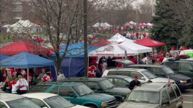 crowd of ohio state university college football fans walking campus sidewalk next to line of street lights parked cars - ohio state university stock videos & royalty-free footage