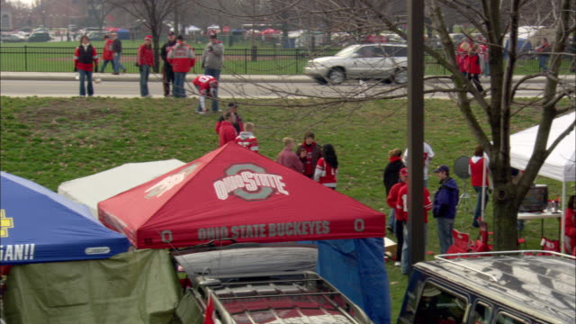 xws crowd of ohio state university college football fans walking campus sidewalk next to line of street lights parked cars slo zi crowd walking - ohio state university stock videos & royalty-free footage