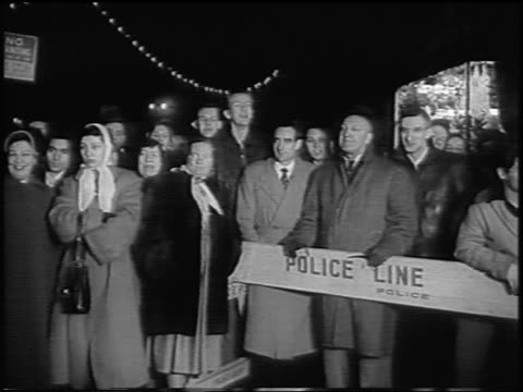 """crowd of onlookers behind police line at premiere of """"the benny goodman story"""" / news. - 1955 stock videos & royalty-free footage"""