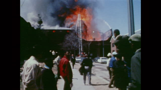 a crowd of onlookers gather to watch a roaring fire on 16th street in dc as firefighters attempt to tackle the huge blaze - 1968年点の映像素材/bロール