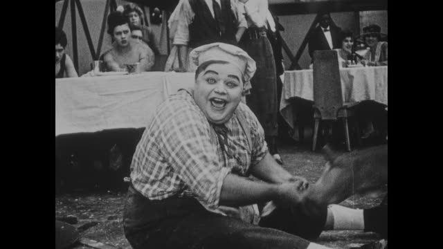 vidéos et rushes de 1918 crowd of onlookers laugh as angry drunk intruder attacked by restraint dog before running away - mordre