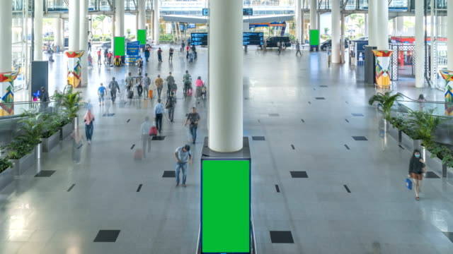 tl: crowd of passengers walking with green screen of billbroad in the kualanamu international airport, indonesia - tabellone video stock e b–roll